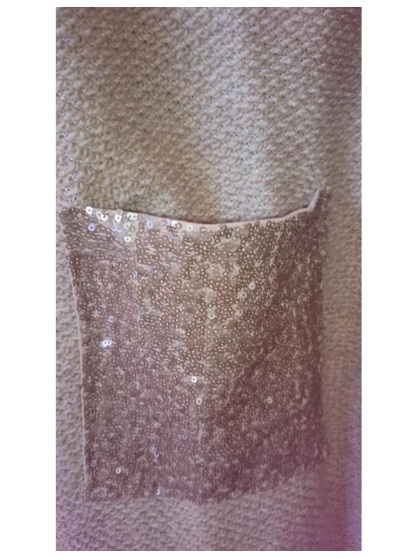 Detalj av den strassklädda fickan på jackan